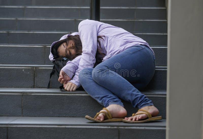 Oung压下了并且陶醉了亚裔学生妇女或少年女孩坐街道楼梯醉酒或高在药物遭受 免版税库存照片