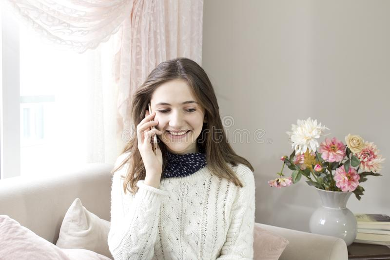 Oung愉快的妇女在家坐沙发,当谈话在电话时 免版税图库摄影