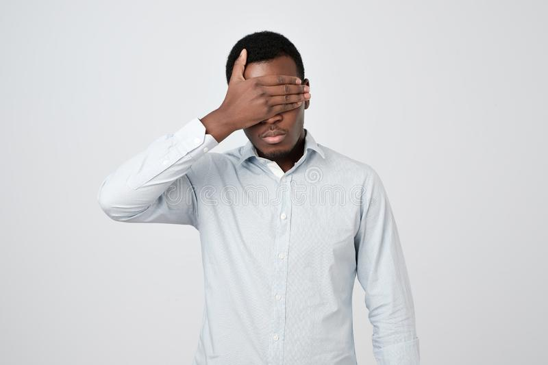 Oung african man in white shirt covering eyes stock photography