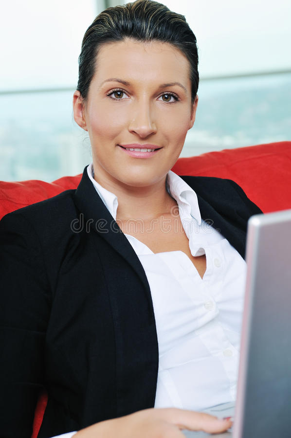 Oung business woman working on laptop at home. Young business woman working on laptop at home in confort bright apartment royalty free stock photos