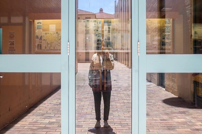 He girl takes pictures in the window on a camera royalty free stock images
