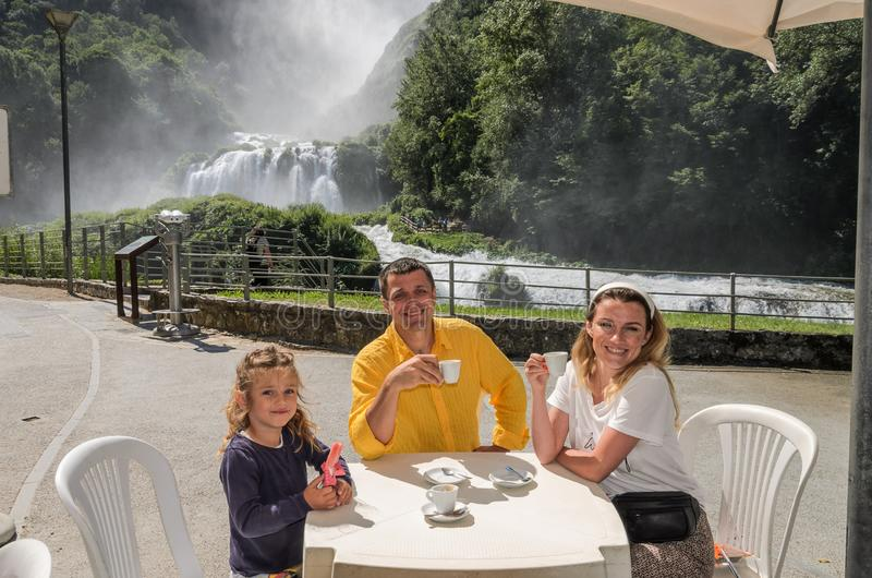 Oung happy family mom, dad and daughter are drinking coffee and eating ice cream at a table in a cafe on the background of a water royalty free stock images