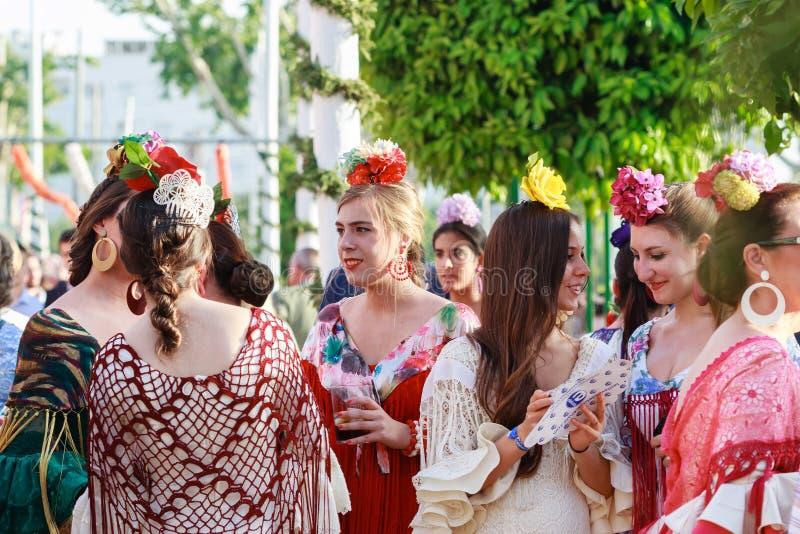 Oung kvinnor som bär traditionell flamenco, klär på April Fair Seville arkivfoto