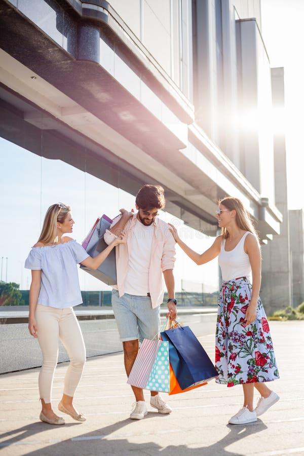 Oung mężczyzna niesie wszystkie torby podczas gdy dwa dziewczyny są roześmiani i żartujący jego stroną zdjęcia stock