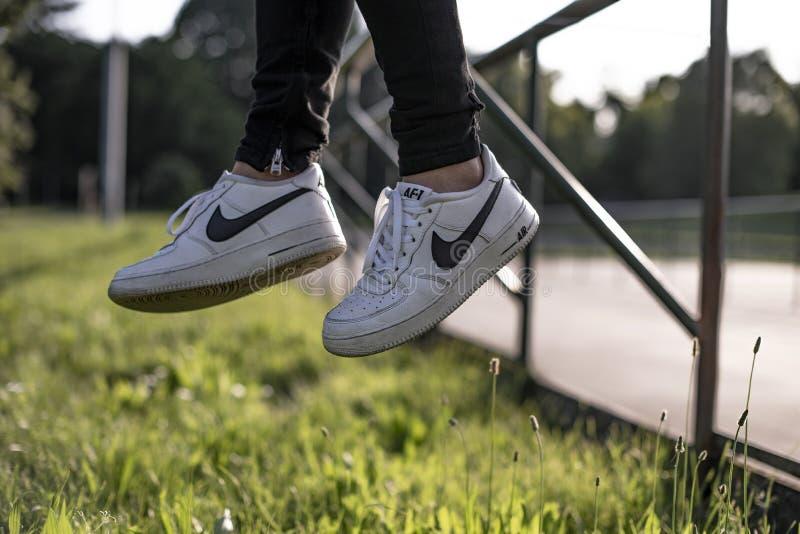 Oung man bar ett par Nike Air Force royaltyfri foto