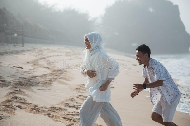 Oung man och kvinna på stranden arkivfoto
