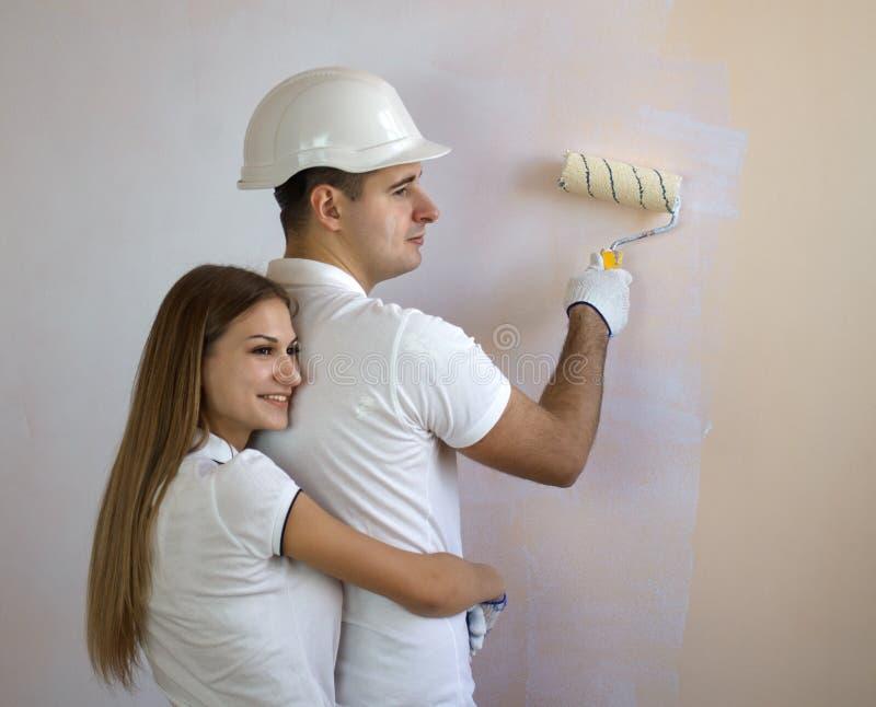 Oung para maluje wewnętrzną ścianę nowy dom fotografia royalty free