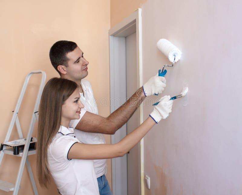 Oung para maluje wewnętrzną ścianę nowy dom obrazy royalty free