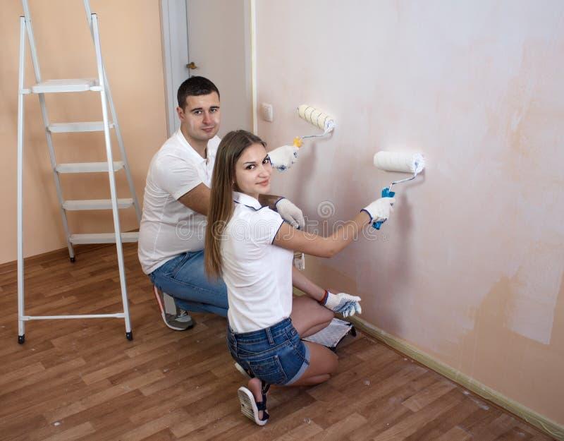 Oung para maluje wewnętrzną ścianę nowy dom obrazy stock