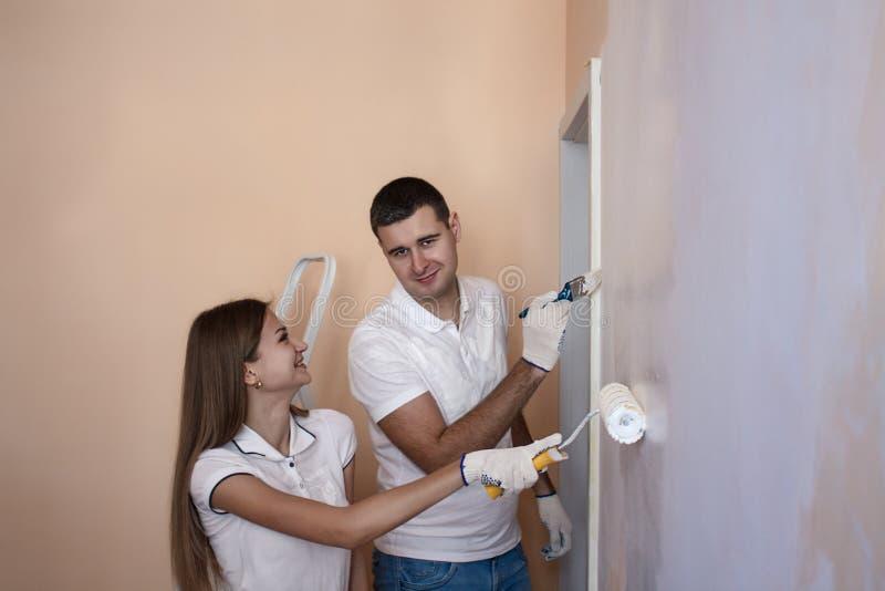 Oung para maluje wewnętrzną ścianę nowy dom zdjęcia royalty free