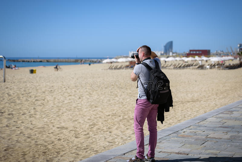 Oung photographer is making photos at Barceloneta beach in Barcelona Spain. royalty free stock photos