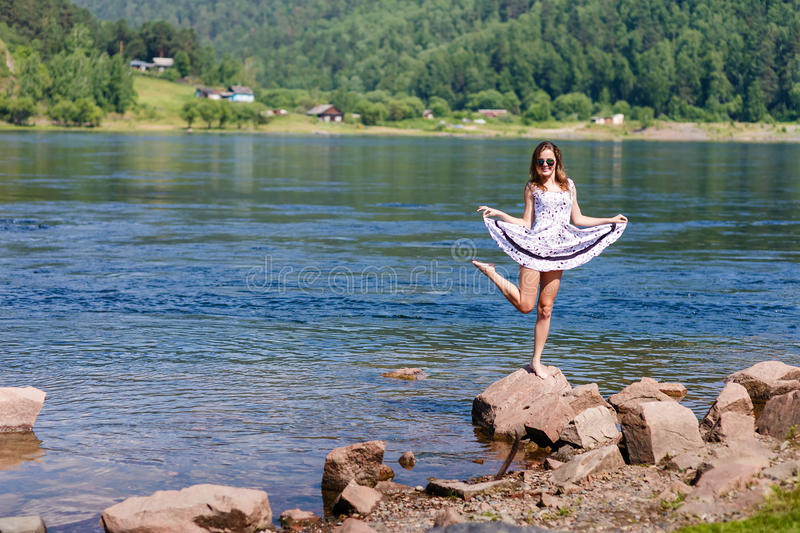 Oung, girl in a dress on the river bank, rocks royalty free stock images
