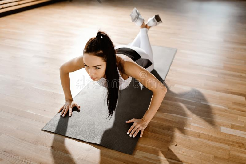 Oung slim dark-haired girl dressed in white sports clothes is doing push ups in the gym royalty free stock photography