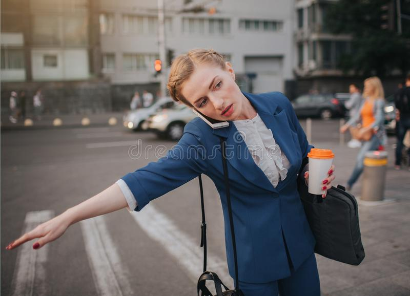 Oung stylish businesswoman with coffee cup catching a taxi. Woman doing multiple tasks. Multitasking business woman. royalty free stock images