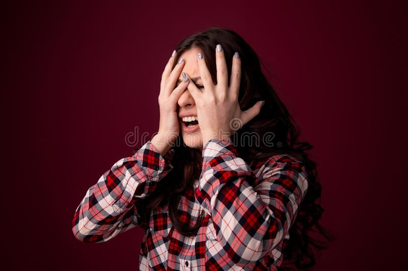 Oung woman covering her eyes isolated on black background royalty free stock photography