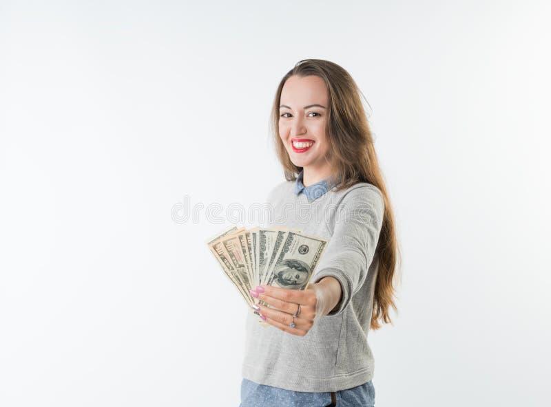 Oungs-Frau, die Dollar hält, wechseln und das glückliche Lächeln lokalisiert ein stockfotos