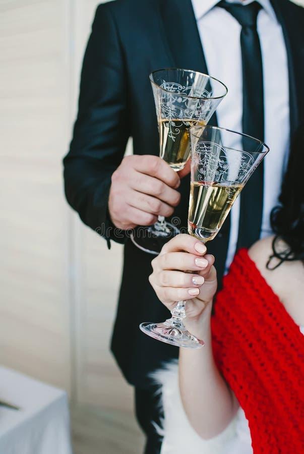 Oungs-Jungvermählten, die elegante Gläser klirren stockfotografie