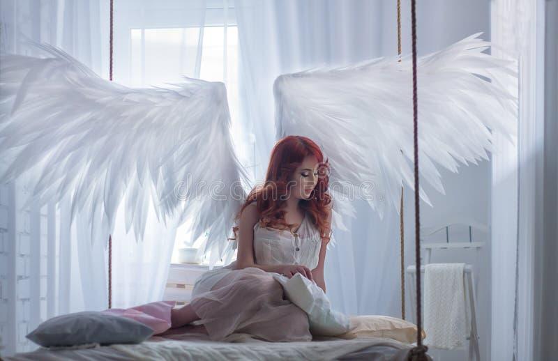 Oungs-Modell mit offenen Engelsflügeln und Rosa kleiden das Sitzen auf hängendem Bett stockbild