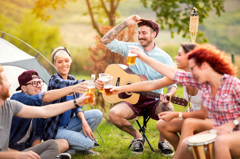 Oungsters tapping with glasses of beer in camp. YJoyous youngsters tapping with glasses of beer in camp on open air royalty free stock image