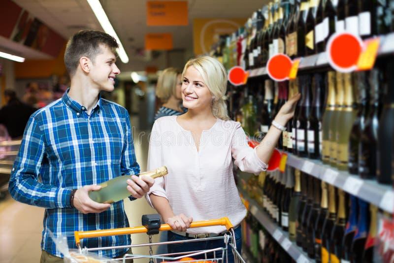Ouple  Ñ клиентов покупая на разделе вина в супермаркете стоковое изображение rf
