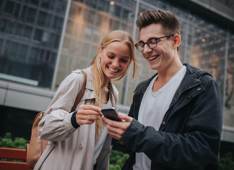 Ouple или смеяться над друзей смешной и иметь потеху с умным телефоном в большой улице города стоковая фотография rf