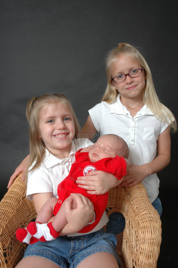 Our Baby Brother. Two young sisters on a black background holding and looking at their new baby brother royalty free stock photography