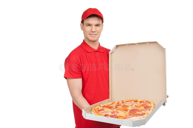 Our best pizza for you. Young cheerful pizza man holding an open. Pizza box and smiling while isolated on white royalty free stock image