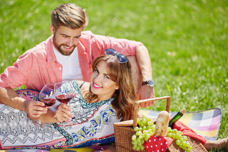 Our first anniversary. A photo of young, happy couple celebrating their anniversary on the picnic at the park royalty free stock image