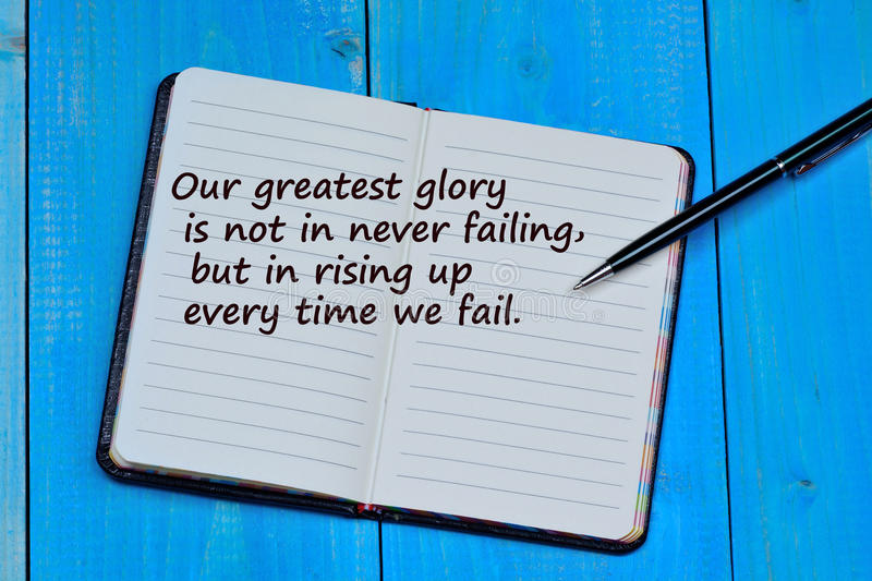 Our greatest glory is not in never failing but in rising uo every time we fail. On notebook royalty free stock photo