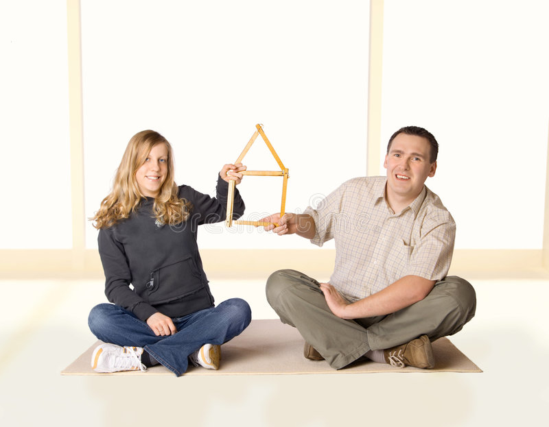Our Home. Yong girl and man holding a house made of ruler