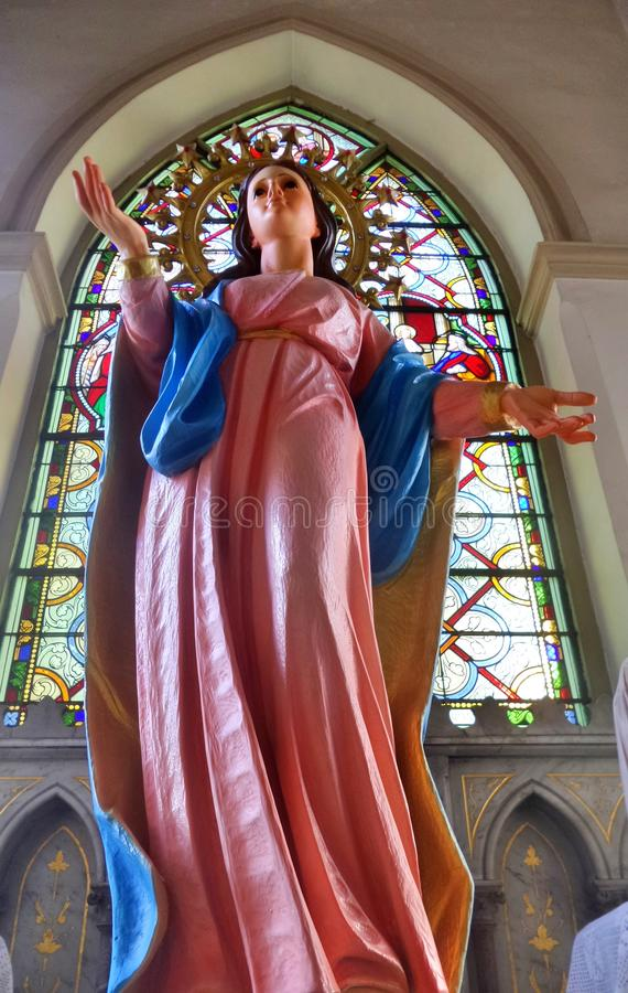 Our lady sculpture and colourful stainglass window in Rosary Kalawar Church Bangkok stock image
