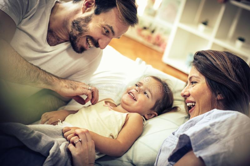 Our morning begins with a smile and fun. Young happy family in bed. Space for copy. Close up stock image