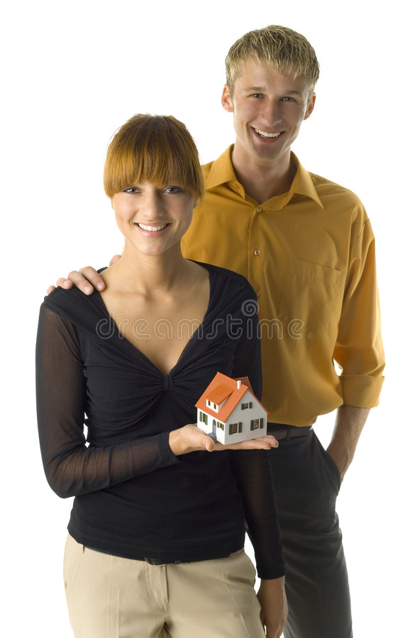 Our new home. Young couple looking happy. Woman is holding house miniature. They're looking at camera. Front view, white background stock image
