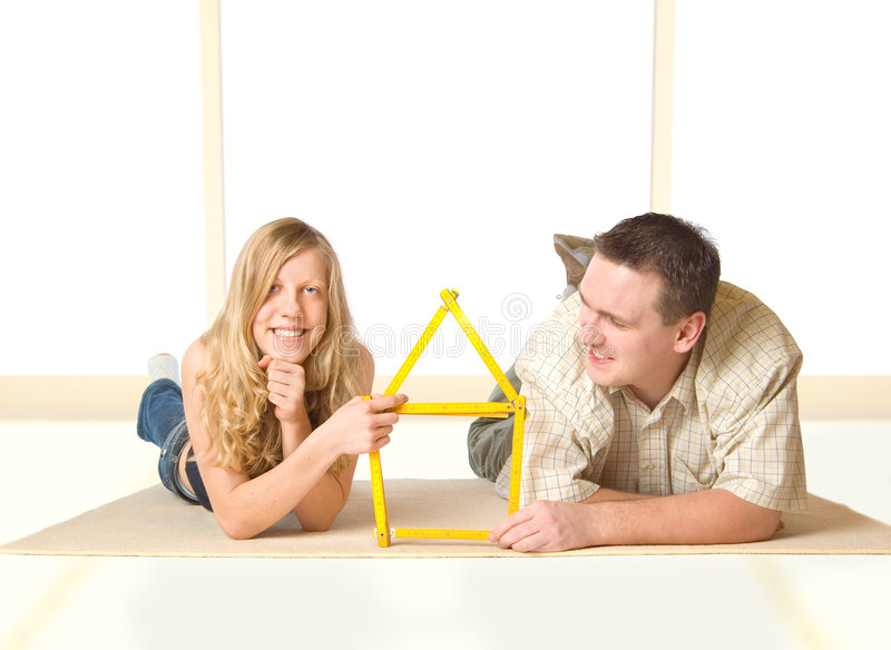 Our New House. Yound girl and a man showing a house made of ruler