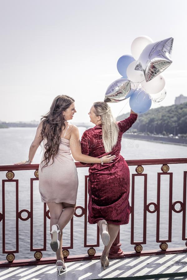 Delighted positive women standing on the bridge stock photography