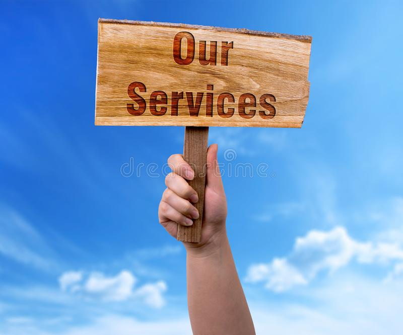 Our services wooden sign. A woman holding our services wooden sign on blue sky background royalty free stock image