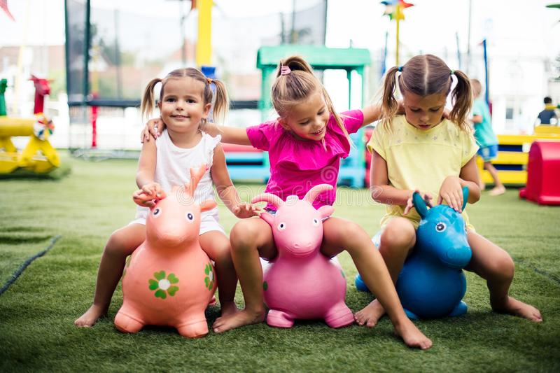 Our time. Three little girls playing in playground. Space for copy stock photography