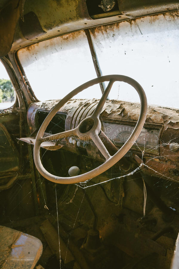 Old rusted truck steering wheel with spider web stock photo