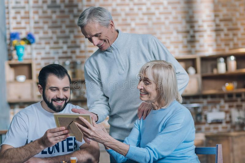 Alert aged spouses showing photos to a young man royalty free stock photo