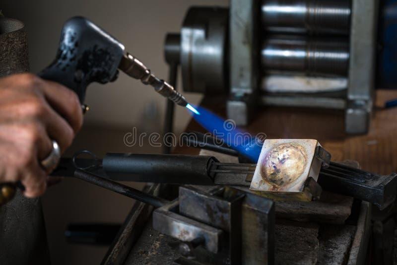 Ourives que usam um maçarico no cadinho: grões de prata de derretimento fotografia de stock