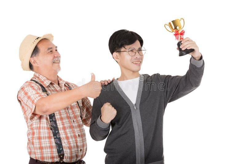 Ouro asiático do copo da posse do homem novo fotos de stock royalty free