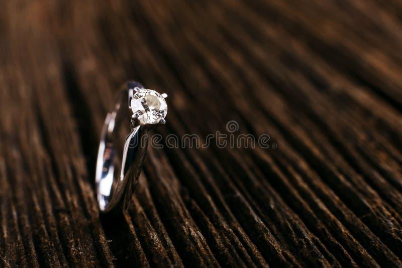 Ouro branco e anel de noivado do diamante da platina Em uma tabela de madeira o imagens de stock royalty free