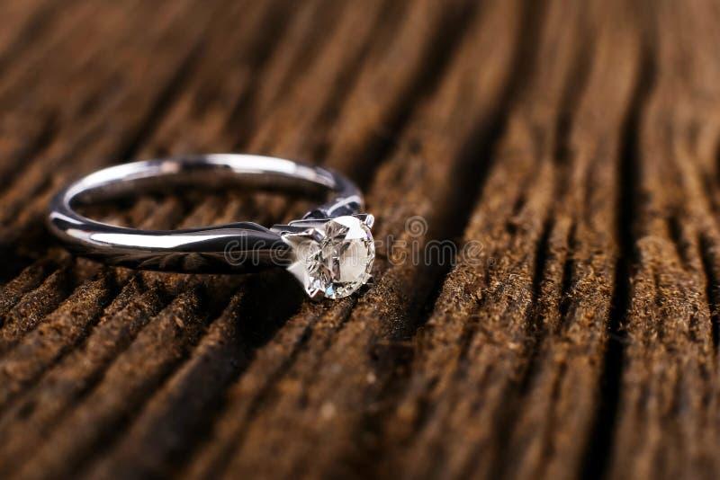 Ouro branco e anel de noivado do diamante da platina Em uma tabela de madeira o foto de stock royalty free