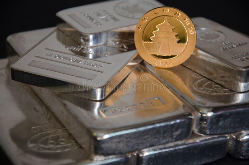 Ouro chinês Panda Coin nas barras de prata fotos de stock royalty free