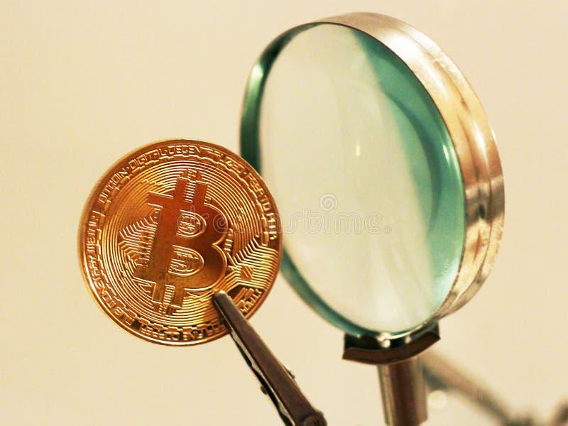 Ouro de Bitcoin e a ferramenta da lente de aumento foto de stock royalty free