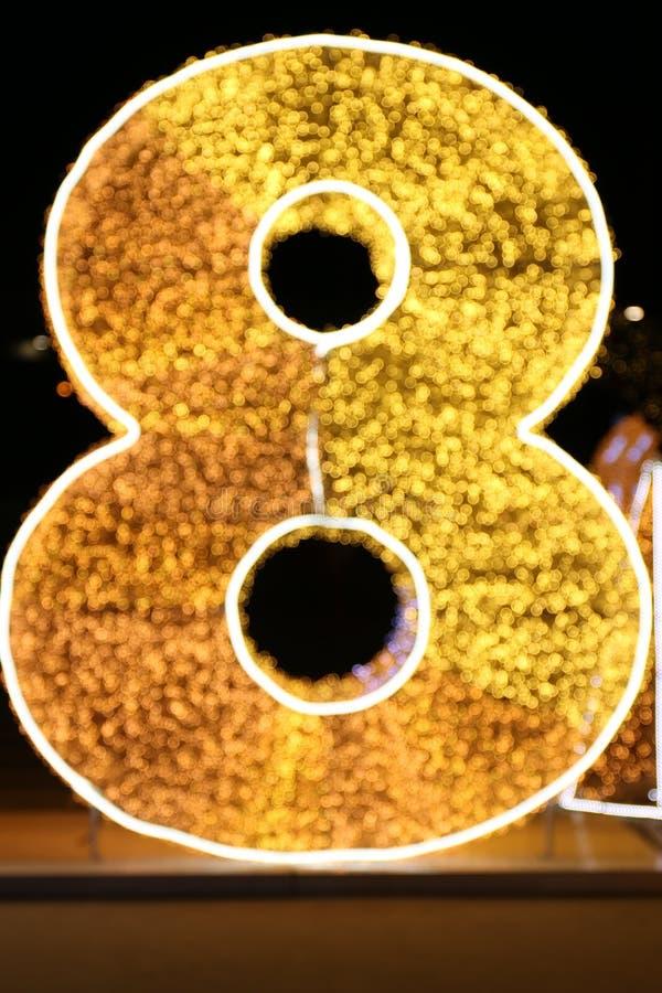 Ouro do número oito do alfabeto, tipo borrado amarelo de brilho da fonte do ouro 8 da letra oito de Bokeh do brilho da iluminação fotografia de stock royalty free