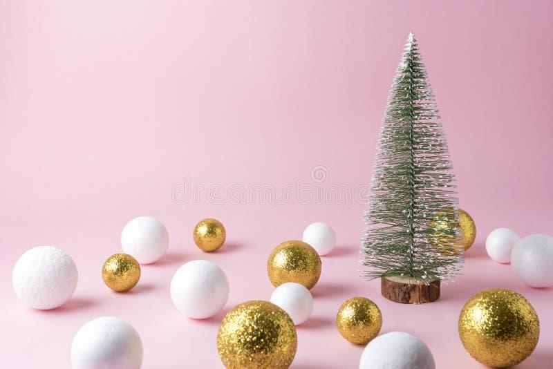 Ouro e decoração branca da bola do brilho com a árvore de Natal pequena no fundo cor-de-rosa imagens de stock royalty free