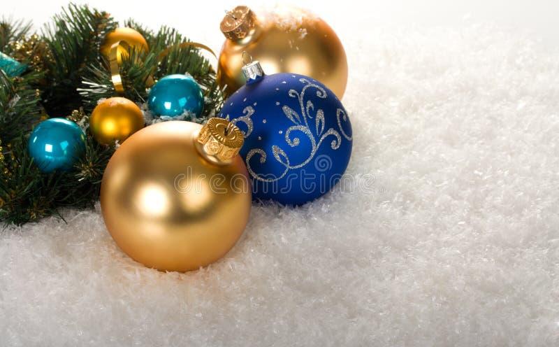 Ouro e esferas azuis do Natal com filial imagens de stock