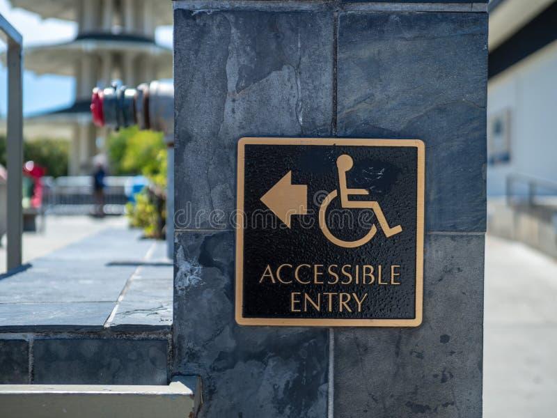 Ouro e postagem de sinal acessível preta da entrada com logotipo da desvantagem da cadeira de rodas com a seta que aponta à esque imagem de stock