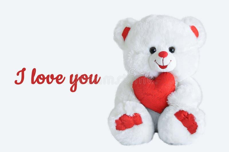 Ours blanc d'ours avec un coeur dans des ses mains Inscription je t'aime image stock